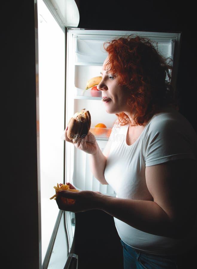 La mujer grande come los alimentos de preparación rápida Muchacha gorda del pelo rojo que mira el refrig interior imagen de archivo