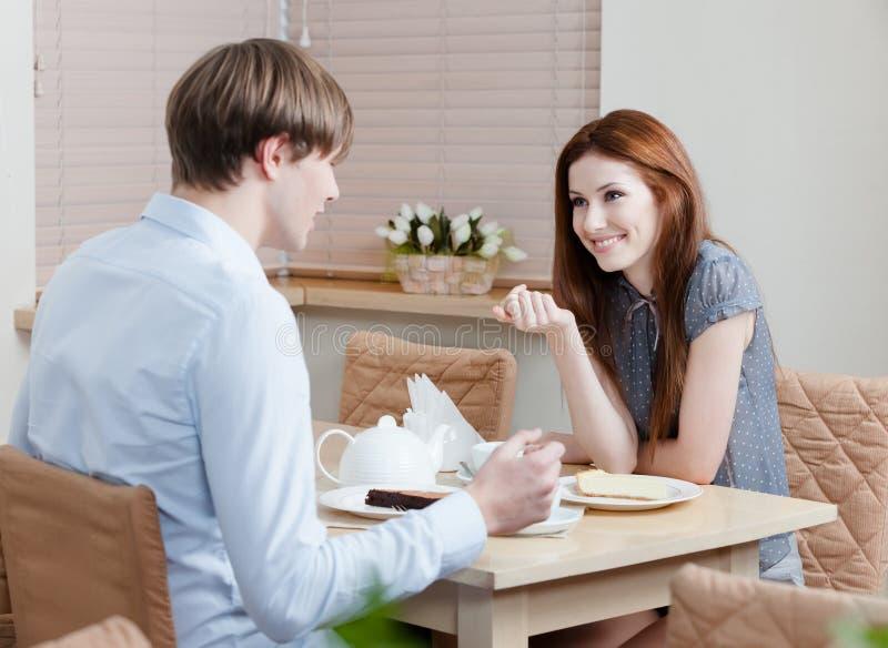 La mujer habla con el hombre en el café imagen de archivo libre de regalías