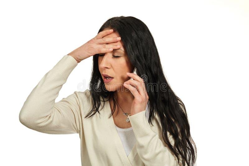 La mujer habla en un teléfono móvil Ella está sintiendo mareada imagen de archivo