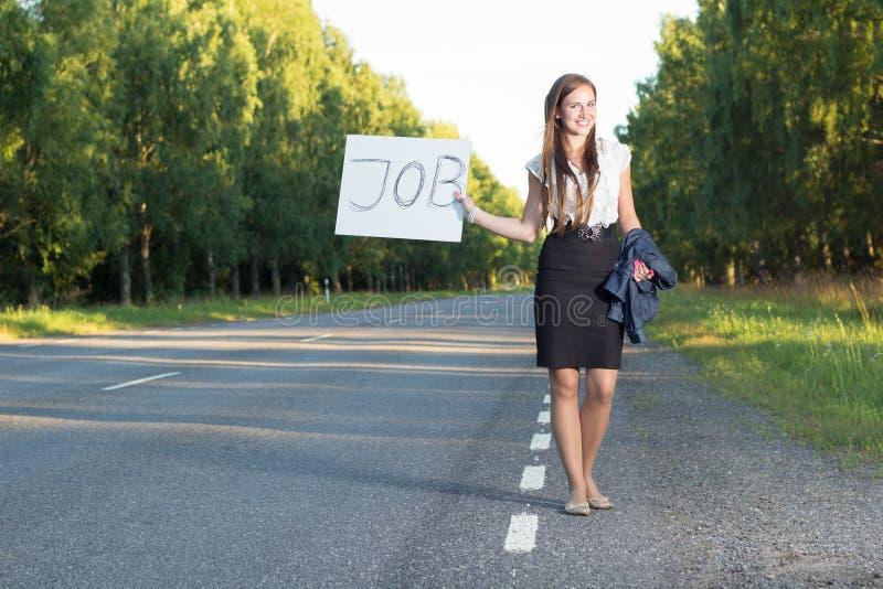 La mujer hace autostop para el trabajo fotografía de archivo libre de regalías
