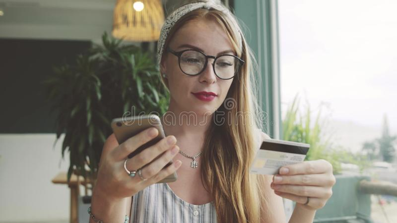 La mujer hace el pago con la tarjeta de crédito y el teléfono móvil Actividades bancarias en línea foto de archivo