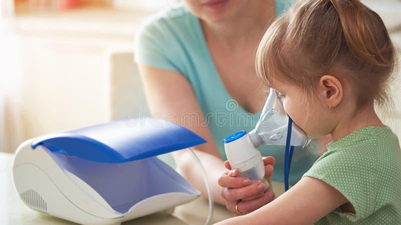 La mujer hace la inhalación a un niño en casa trae la máscara del nebulizador a su cara inhala el vapor de la medicación La mucha imagen de archivo libre de regalías