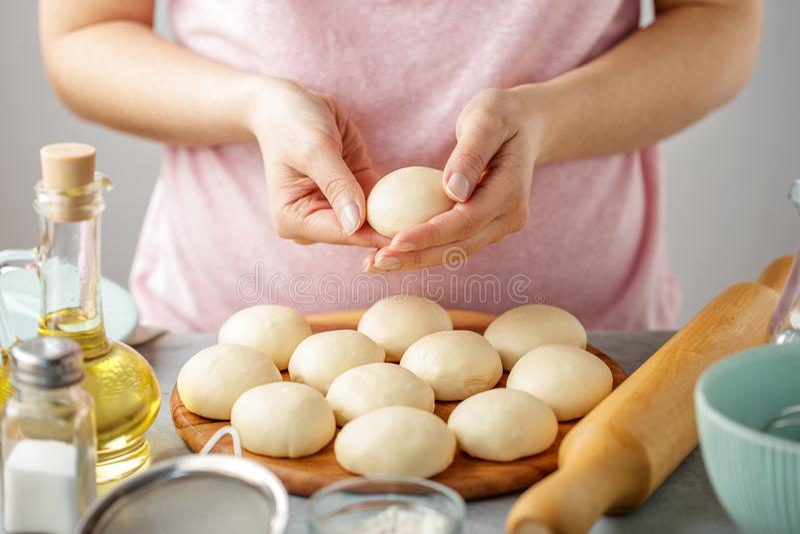 La mujer hace las bolas de la pasta para cocinar el flatbread mexicano foto de archivo