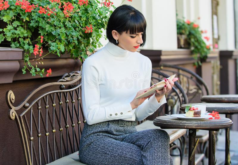 La mujer hace que la bebida goce de la buena terraza del café del libro Literatura para la hembra Libro de la lectura del café de imágenes de archivo libres de regalías