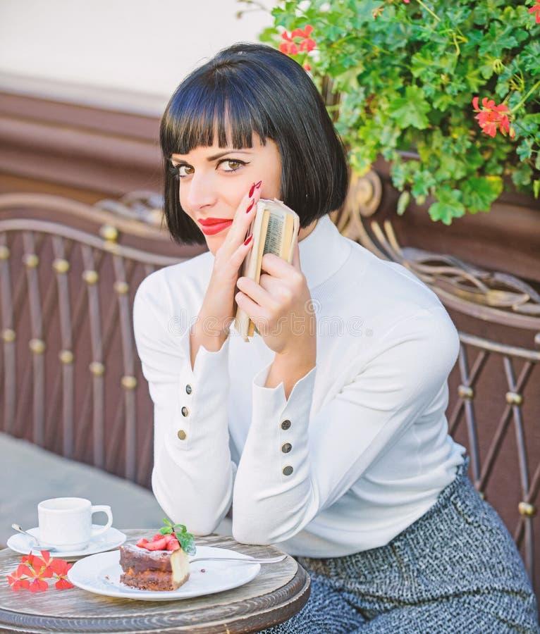 La mujer hace que la bebida goce el leer de la buena terraza del café del libro Literatura moderna para la hembra La señora del n fotografía de archivo