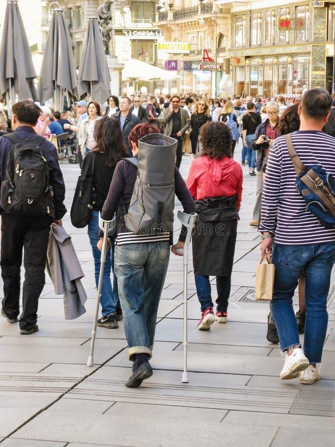 La mujer herida con sus bastones es viajero útil Paseo turístico a través del centro de la ciudad con los bastones que caminan fotografía de archivo