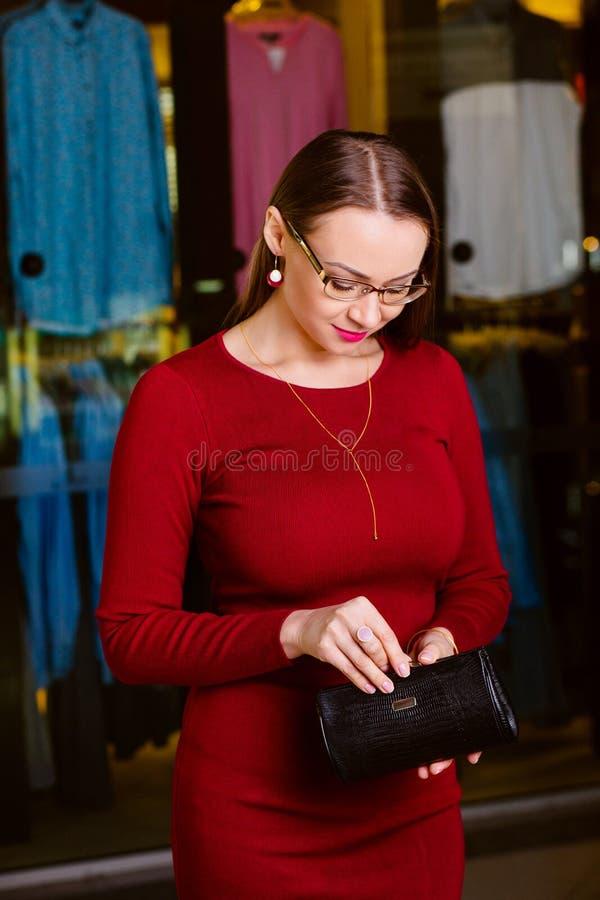 La mujer hermosa abre la cartera Compre la ropa en una tienda imagenes de archivo