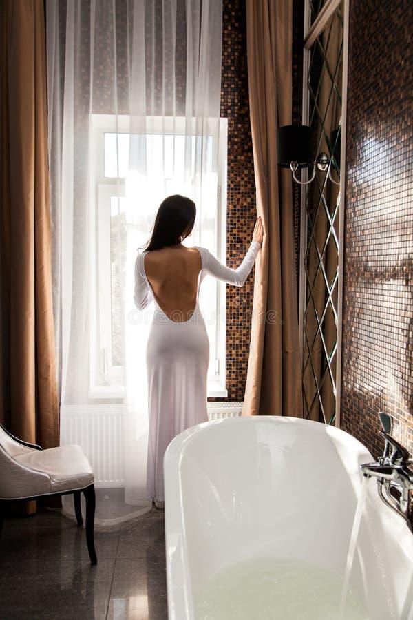 La mujer hermosa abre la cortina y la preparación tomar un baño imagen de archivo libre de regalías