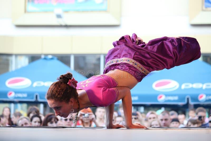 La mujer hermosa adentro está mostrando yoga en la etapa imagen de archivo