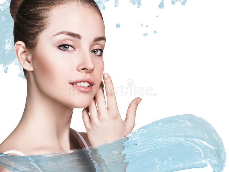 La mujer hermosa adentro salpica del agua azul clara foto de archivo