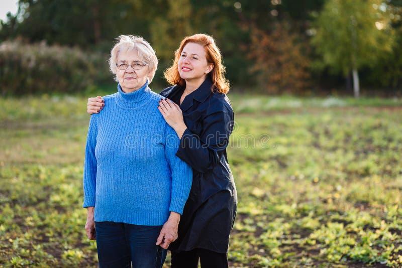 La mujer hermosa adulta abraza suavemente a la madre canosa mayor al aire libre foto de archivo