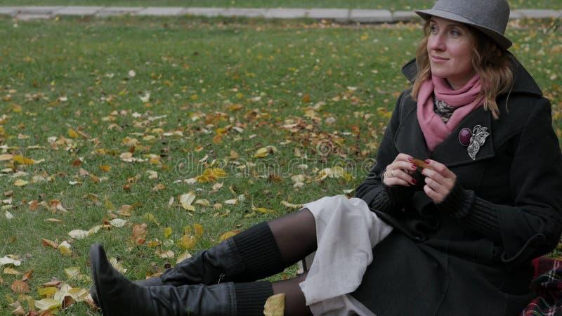 La mujer hermosa adulta en un sombrero camina en el parque del otoño Paseo alegre del otoño imagen de archivo libre de regalías