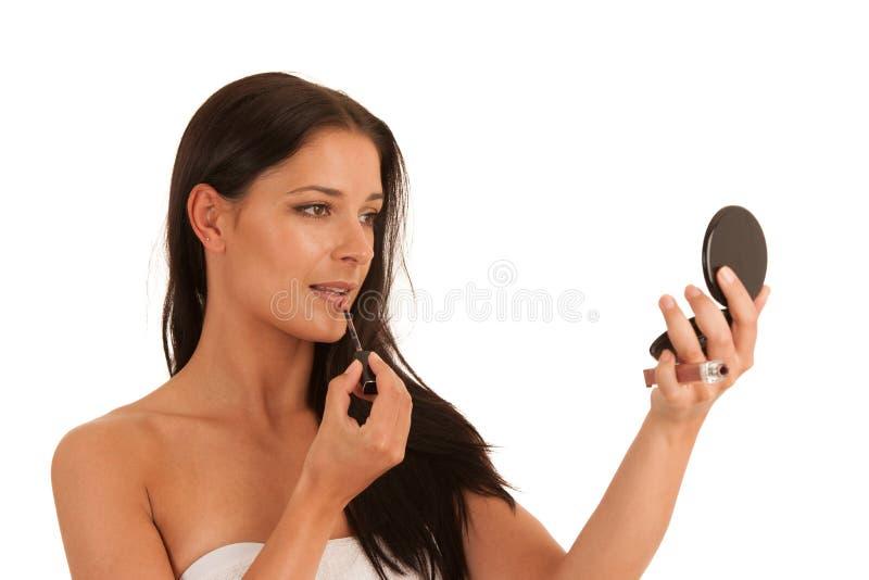 La mujer hermosa aplica lustre del labio aislada sobre el fondo blanco fotografía de archivo
