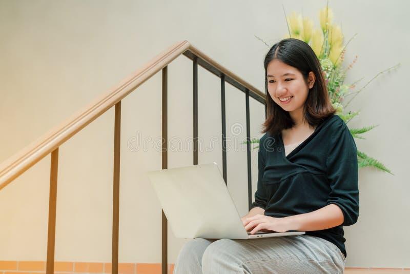 La mujer hermosa asiática del primer que lleva una camisa negra que se sienta en las escaleras en la casa utiliza un ordenador po imagenes de archivo