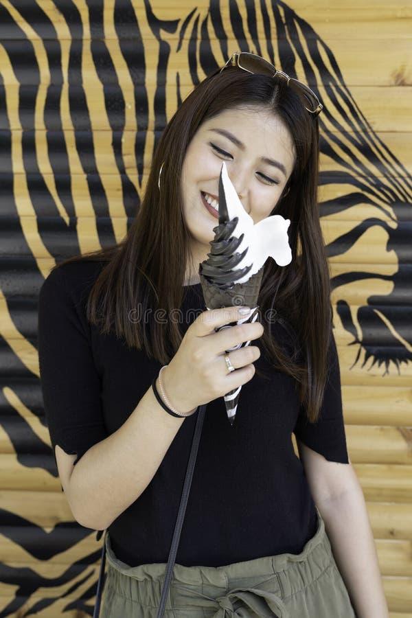 La mujer hermosa asiática goza del cono de helado fotos de archivo libres de regalías