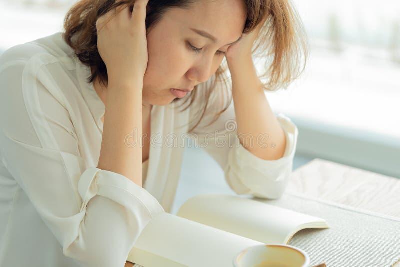 La mujer hermosa asiática leyó los libros por la ventana con la tensión Utilice para concentrar en los libros de lectura, aprendi fotos de archivo