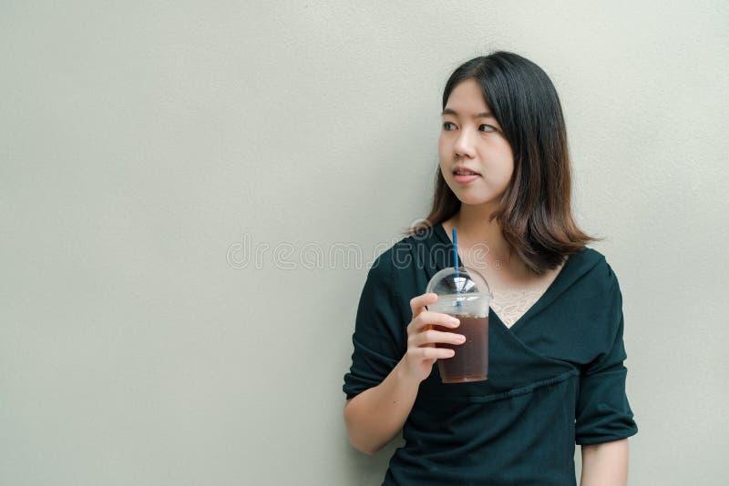 La mujer hermosa asiática puso en una camisa negra, soporte para beber el café frío en la mano con placer foto de archivo