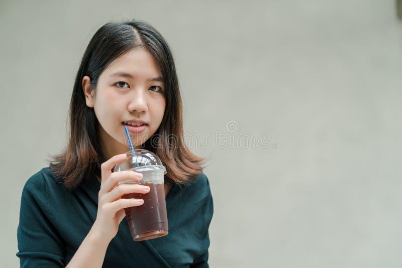 La mujer hermosa asiática puso en una camisa negra, soporte para beber el café frío en la mano con placer foto de archivo libre de regalías