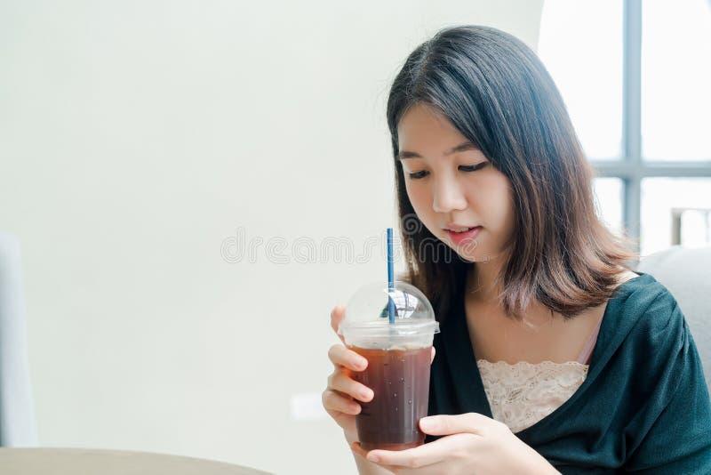 La mujer hermosa asiática puso en una camisa negra, soporte para beber el café frío en la mano con placer imagen de archivo libre de regalías