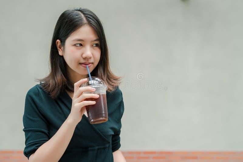 La mujer hermosa asiática puso en una camisa negra, soporte para beber el café frío en la mano con placer imágenes de archivo libres de regalías