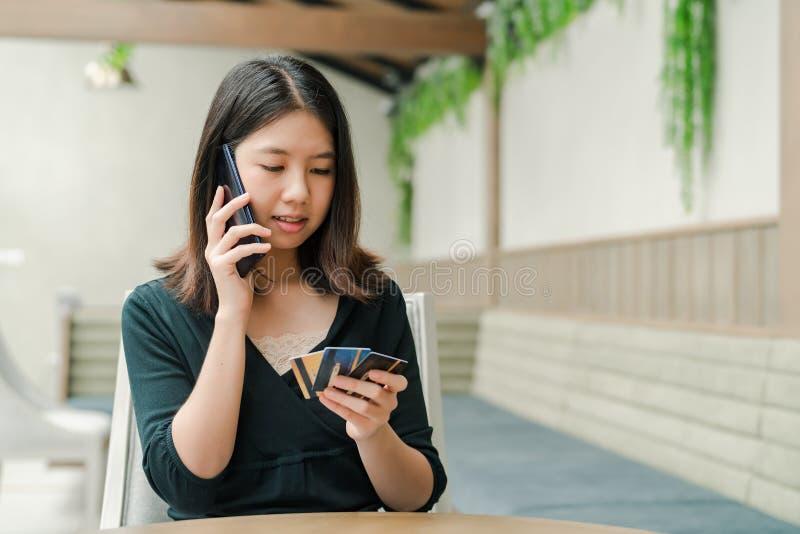 La mujer hermosa asiática que lleva una camisa negra que se sienta en la casa allí es una tarjeta de crédito en su mano y usted e fotos de archivo libres de regalías
