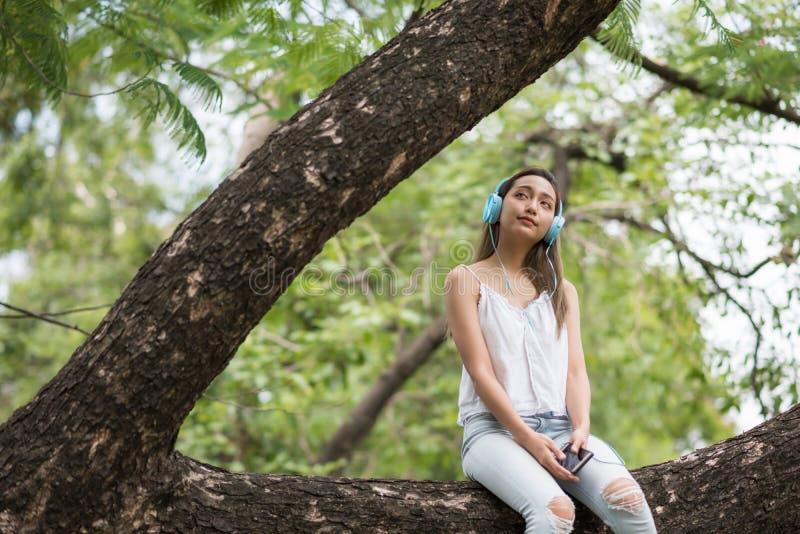 La mujer hermosa asiática se sienta en árbol grande y escucha la música que fluye en línea del smartphone por auriculares de botó fotografía de archivo libre de regalías