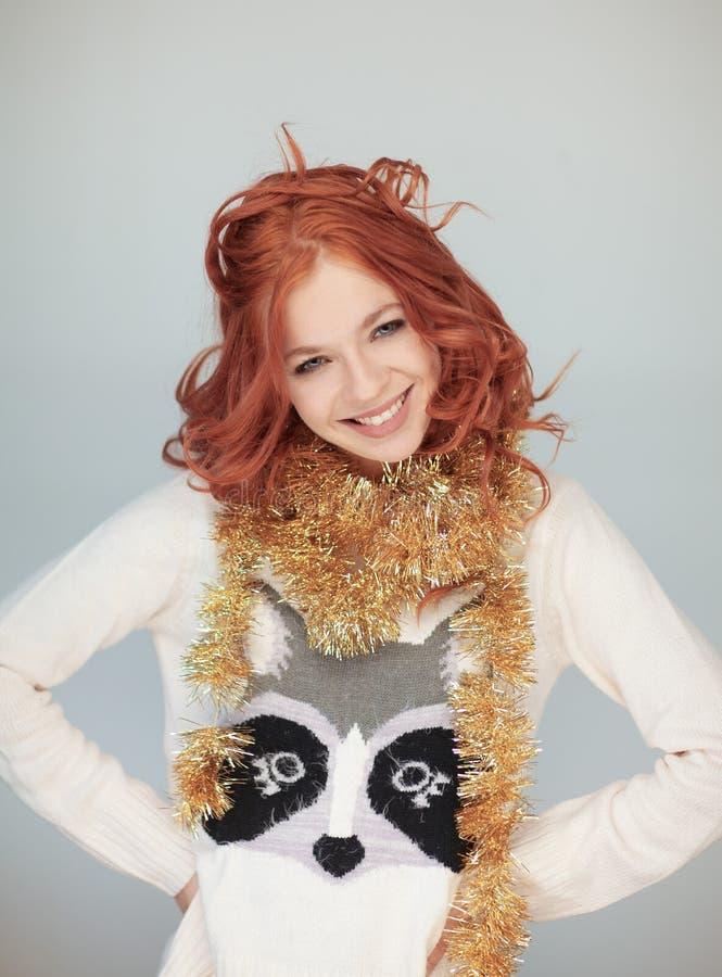 La mujer hermosa con el pelo rizado rojo perfecto y compone en un suéter hivernal del punto de la Navidad foto de archivo