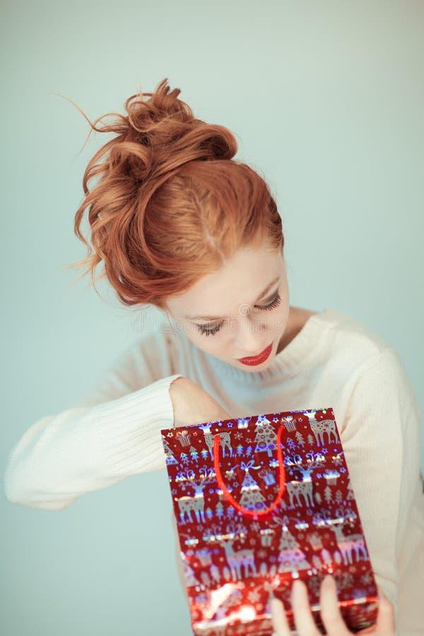 La mujer hermosa con el pelo rizado rojo sostiene un regalo de la Navidad en sus manos imágenes de archivo libres de regalías