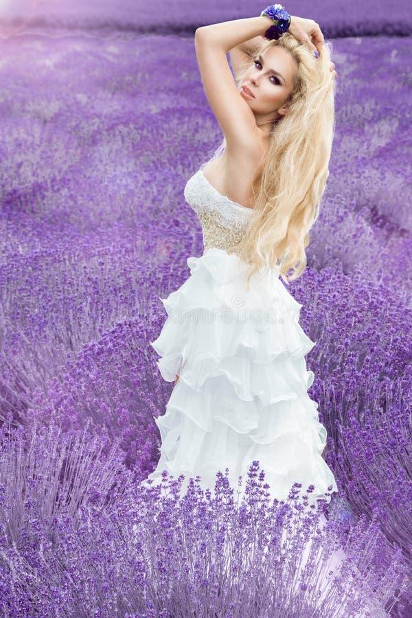 La mujer hermosa con el pelo rubio en un vestido de boda blanco largo hermoso se coloca en un campo con las flores del brezo fotografía de archivo libre de regalías