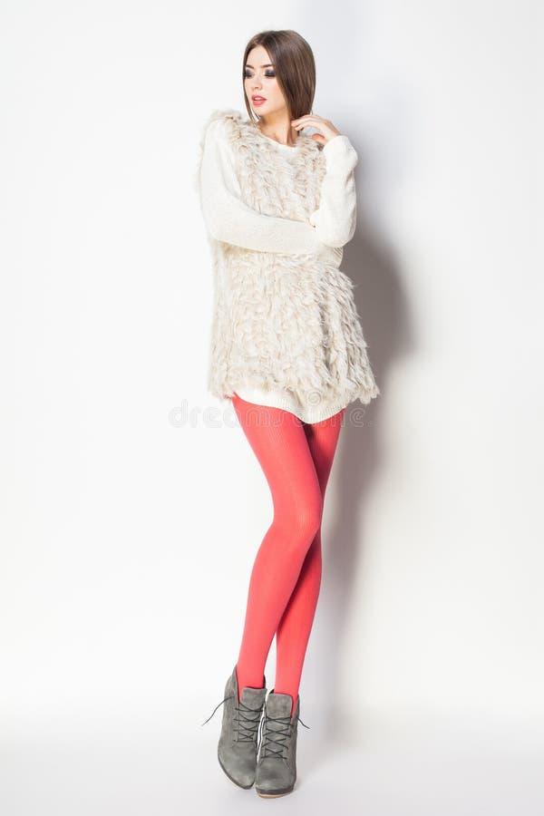 La mujer hermosa con las piernas atractivas largas vistió la presentación elegante en th fotografía de archivo libre de regalías