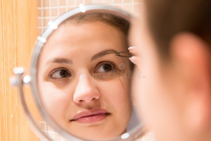 La mujer hermosa con las pinzas est? desplumando las cejas mientras que mira en el espejo en cuarto de ba?o Skincare de la bellez foto de archivo libre de regalías