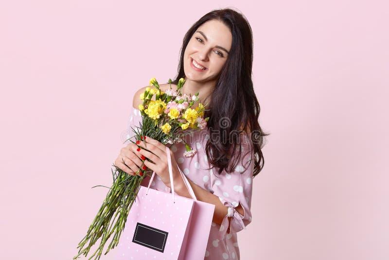La mujer hermosa con sonrisa dentuda, tiene de largo pelo recto oscuro, inclina la cabeza, lleva el ramo de flores y el bolso con fotos de archivo libres de regalías