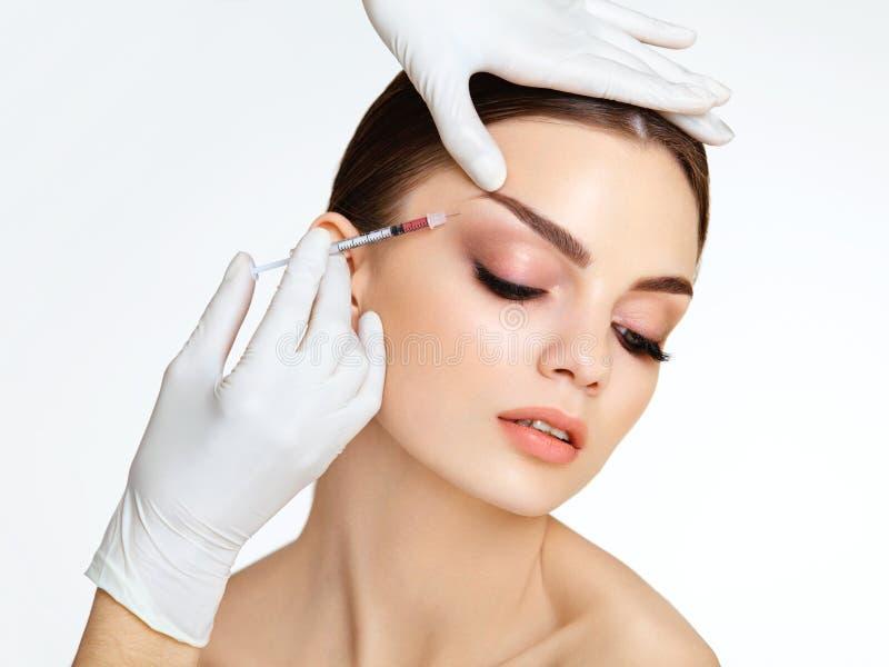 La mujer hermosa consigue inyecciones. Cosmetología. B fotografía de archivo libre de regalías