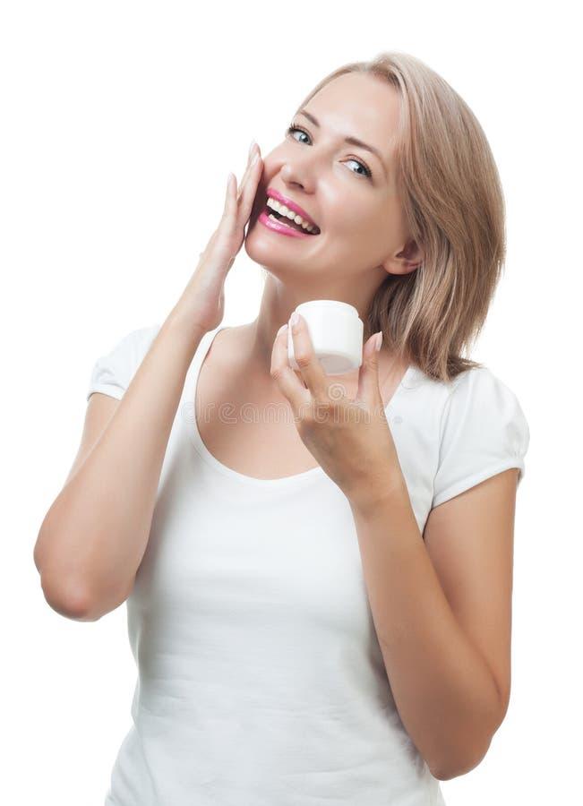 La mujer hermosa consigue la crema en la cara aislada en blanco foto de archivo