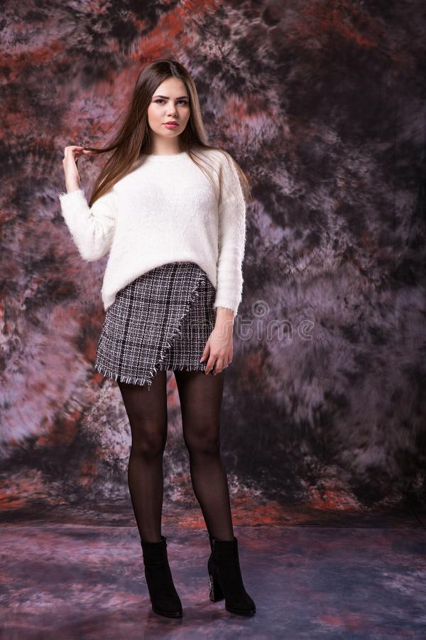La mujer hermosa coqueta del tamaño extra grande en un suéter de color claro y una falda en un mármol coloreó el fondo imagenes de archivo