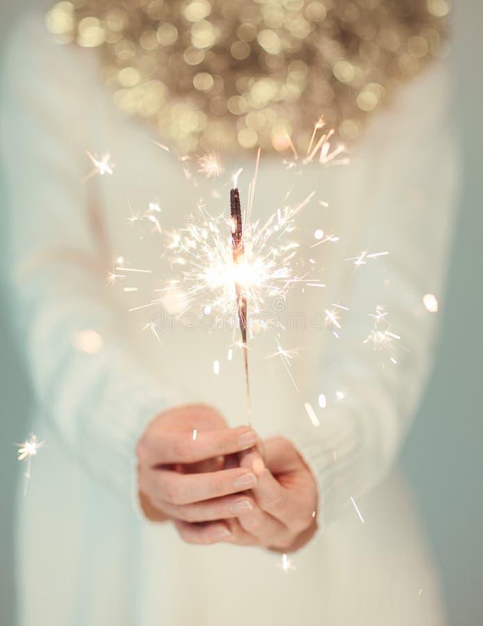 La mujer hermosa da llevar a cabo las luces de la bengala, suéter acogedor, brillante del invierno con la guirnalda de oro de la  fotos de archivo libres de regalías