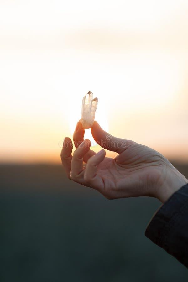 La mujer hermosa da sostener pocos cristales de cuarzo en la luz del sol foto de archivo libre de regalías