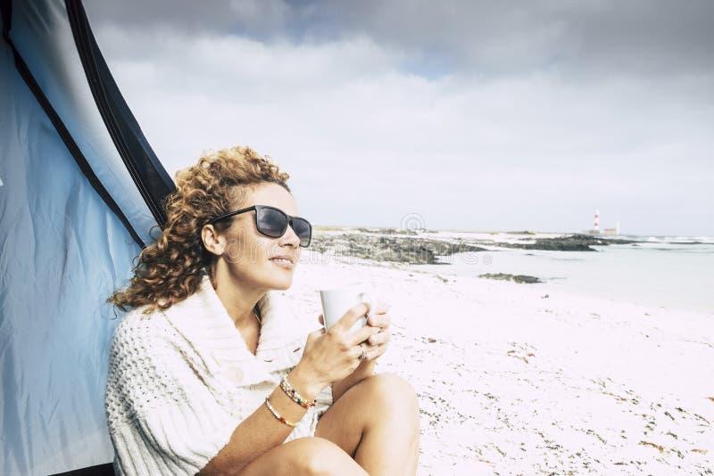 La mujer hermosa de la Edad Media se sienta fuera de una tienda en la sensación al aire libre que acampa de la playa libre la beb imágenes de archivo libres de regalías
