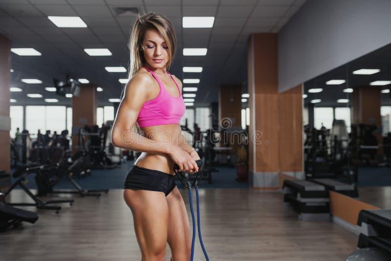 La mujer hermosa de la aptitud ejecuta ejercicio con el ampliador en gimnasio S imágenes de archivo libres de regalías