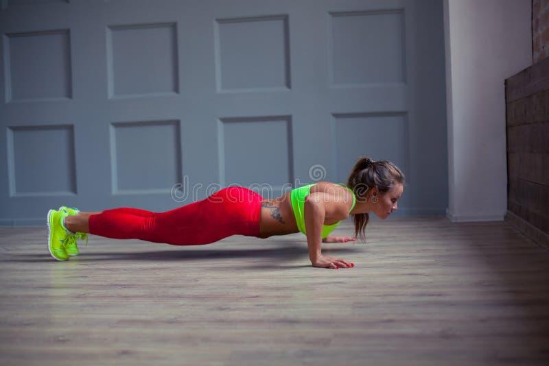 La mujer hermosa de la aptitud está haciendo pectorales en el gimnasio, foto de archivo