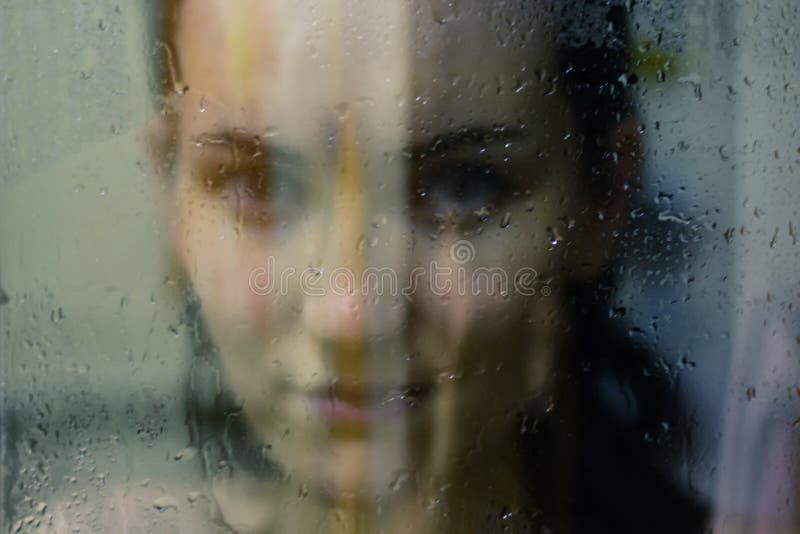 La mujer hermosa detrás del vidrio con agua cae mirar directamente la cámara La muchacha toma una ducha, voyeurism imagen de archivo