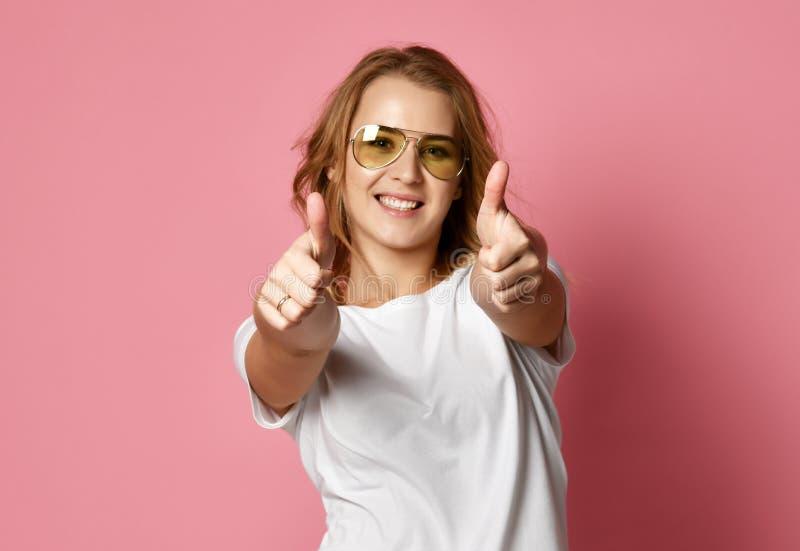 La mujer hermosa en la camiseta blanca y las gafas de sol tipo aviador muestran los pulgares encima de la muestra en rosa fotografía de archivo libre de regalías