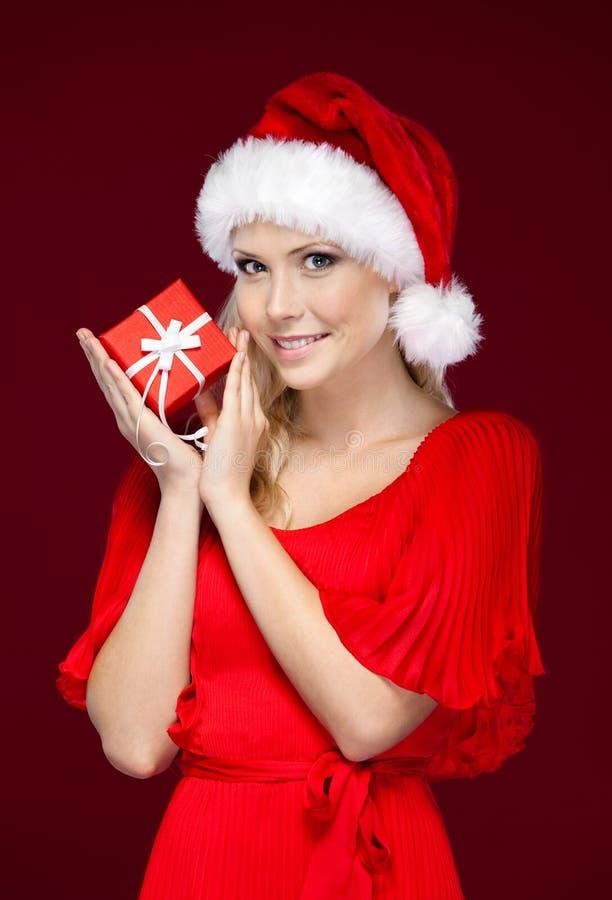 La mujer hermosa en casquillo de la Navidad da un regalo fotografía de archivo libre de regalías