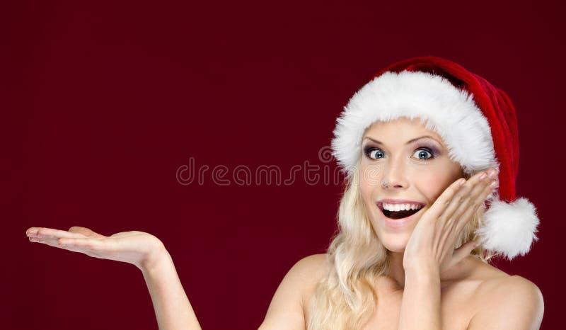 La mujer hermosa en casquillo de la Navidad gesticula la palma para arriba foto de archivo libre de regalías