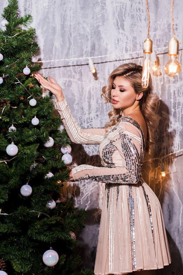 La mujer hermosa en el Año Nuevo interior se viste para arriba Árbol de navidad foto de archivo libre de regalías