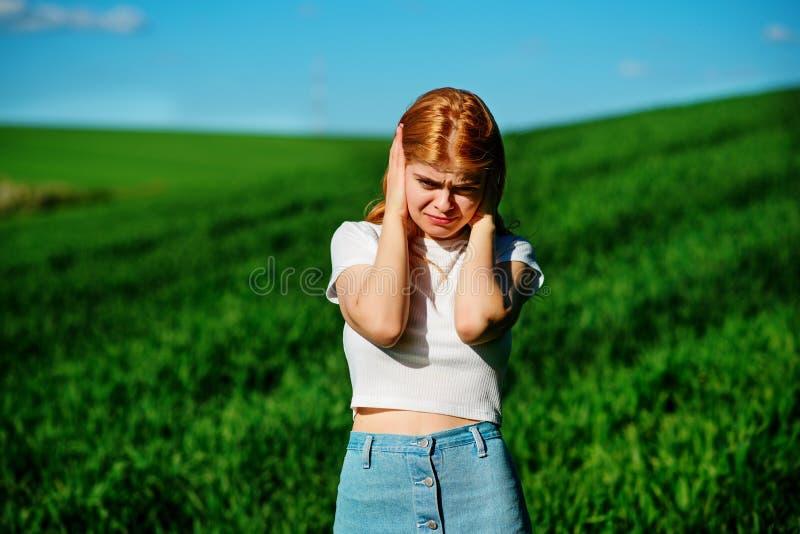 La mujer hermosa en el campo se está cerrando los oídos con sus manos: imagen de archivo libre de regalías