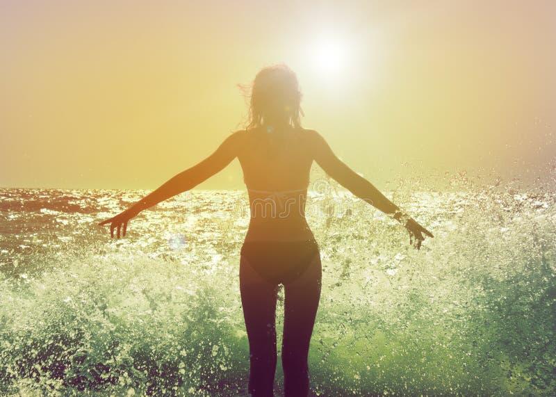 La mujer hermosa en el mar agita vista posterior foto de archivo