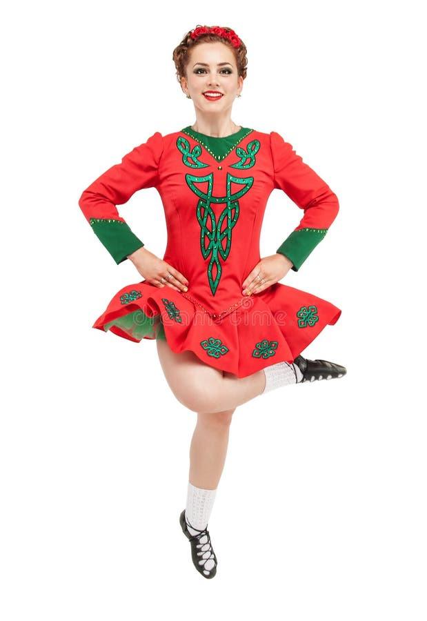 La mujer hermosa en el vestido rojo para el irlandés baila el salto aislado imagenes de archivo