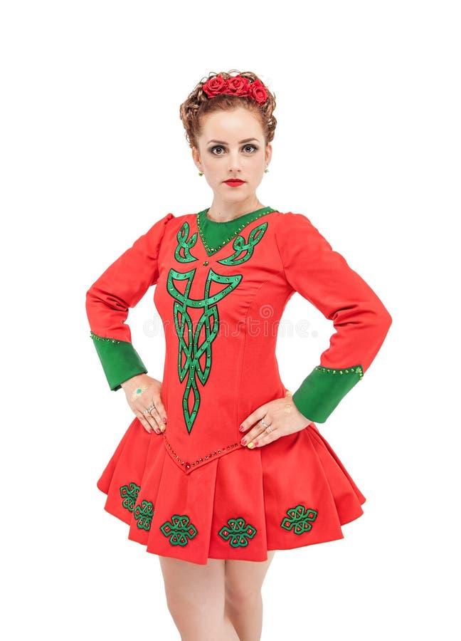 La mujer hermosa en el vestido rojo para el irlandés baila aislado foto de archivo