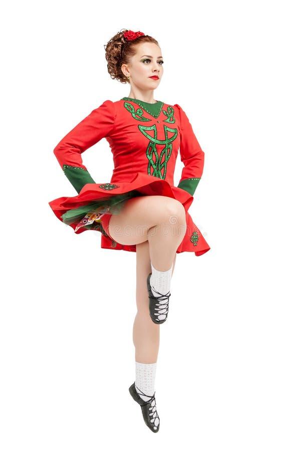 La mujer hermosa en el vestido rojo para el irlandés baila el salto aislado foto de archivo libre de regalías